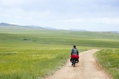 Man Riding Bike through Mongolian Steppes. A rides bikes down a dirt road through the Mongolia steppe landscape Stock Photo