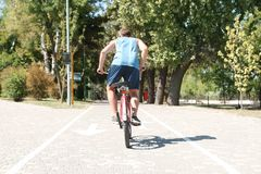 Man riding bike outdoors. On sunny day stock image