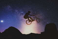 Man riding a bike performing a trick against on Mountain with Milky way. Stock Photos