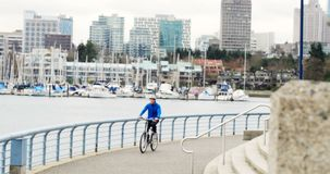 Man riding a bike on the promenade near the harbor 4k. Man riding a bike on the promenade near the harbor in city 4k stock footage
