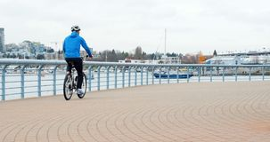 Man riding a bike on the promenade near the harbor 4K 4k. Man riding a bike on the promenade near the harbor in city 4K 4k stock footage