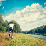 Man Riding a Bike on River Bank. Nature Background Stock Photography