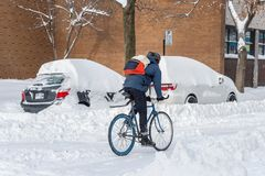 A man is riding a bike during snow storm royalty free stock photography