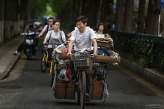 Man riding a bike to buy scrap. In May 2017, a man in Nanjing, China, bought scrap goods, riding a modified bicycle, loaded with used items on his bicycle royalty free stock photography