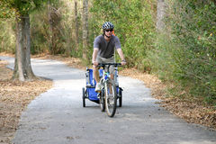 Man riding bike on trail pulling trailer. Caucasian father and son enjoying a bike ride on a country bike trail Stock Photos
