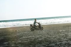 Man Riding Black and Gray Motor Scooter on Beach stock photography