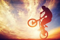 Man riding a bmx bike performing a trick against sunset sky Royalty Free Stock Photo