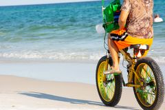 Man Riding a Bycicle on White Sand on Blur Ocean Water Background. Destin Beach, Florida. Man Riding a Bycicle on White Sand on Blur Ocean Water Background stock image