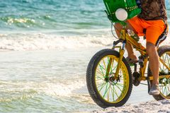 Man Riding a Bycicle on White Sand on Blur Ocean Water Background. Destin Beach, Florida. Man Riding a Bycicle on White Sand on Blur Ocean Water Background royalty free stock photography