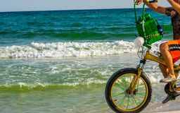 Man Riding a Bycicle on White Sand on Blur Ocean Water Background. Destin Beach, Florida. Man Riding a Bycicle on White Sand on Blur Ocean Water Background stock photography