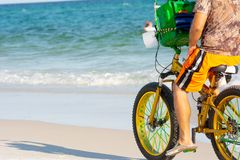 Man Riding a Bycicle on White Sand on Blur Ocean Water Background. Destin Beach, Florida. Man Riding a Bycicle on White Sand on Blur Ocean Water Background royalty free stock image