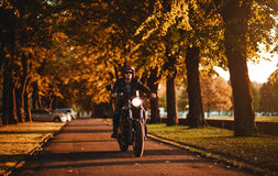 Man riding a cafe-racer motorcycle royalty free stock photography