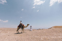 Man Riding Camel on Desert Under Blue Sky during Daytime Royalty Free Stock Photo
