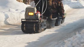 Man riding on crawler mini snowmobile with a trailer and a passenger on a winter road. Specialized vehicle Stock Images
