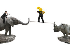 Man riding elephant against rhinoceros another man carrying doll Royalty Free Stock Photography