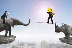 Man riding elephant against rhinoceros another man carrying euro Stock Photos