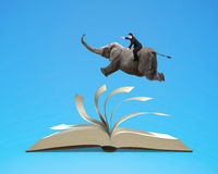 Man riding elephant flying on top flipping pages of open book is Stock Photos