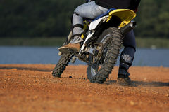 Man riding enduro motorcycle on dirt field Stock Images
