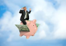 Man riding flying piggy bank on wings of money showing financial and business success Stock Photography