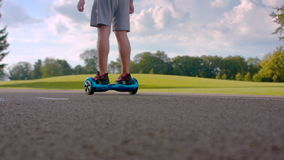 Man riding on gyro scooter on asphalt road. Man driving self balancing board. Man riding on gyro scooter on asphalt road. Back view of man driving self balancing stock footage