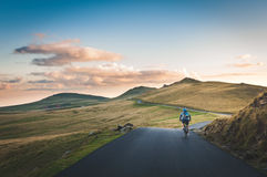 Man Riding His Bicycle Passing Through Mountain Road Stock Images