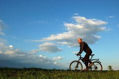 Man riding his bike. At sunset Stock Photo