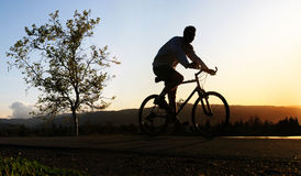 Man riding his bike. At sunset stock photography