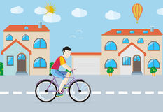 Man riding his bike on the road among buildings Stock Images