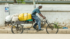 Man riding his customised bicycle fitted with a loaded trailer. Dar Es Salaam: April 22: A man rides his customised bicycle fitted with a trailer that is loaded Royalty Free Stock Photography