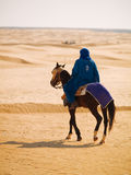 Man riding a horse in the desert Stock Photo