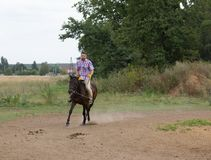 A man riding a horse on the field. stock photography
