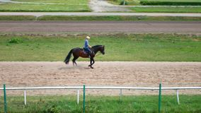 Man riding a horse gallop gracefully on a race track