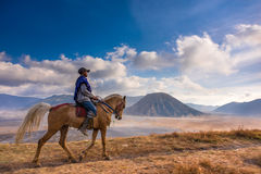 A man riding a horse with Mount Batok in the background.  Stock Image