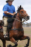 Man riding horse at speed. The man from Snowy Mountains riding a horse at full gallop Royalty Free Stock Photo