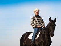 Man riding horse, striped pullover, blue jeans, hat, close up. Beautiful strong man cowboy riding black horse. Has happy  face, striped pullover, blue jeans, hat Royalty Free Stock Photos