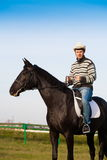 Man riding horse, striped pullover, blue jeans, hat, close up. Beautiful strong man cowboy riding black horse. Has happy  face, striped pullover, blue jeans, hat Stock Image