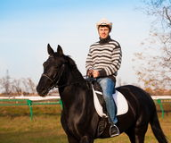 Man riding horse, striped pullover, blue jeans, hat, close up. Beautiful strong man cowboy riding black horse. Has happy  face, striped pullover, blue jeans, hat Stock Images