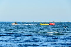 Man riding a jet ski over blue Black Sea water, banana boat. Royalty Free Stock Photography