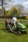 Man on Riding Lawn Mower. White middle-aged man mowing suburban lawn on a riding tractor-style lawn mower.  Green and yellow tractor is set off by yellow Stock Image