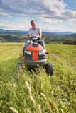 Man riding a lawn tractor Stock Image