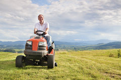 Man riding a lawn tractor. Man mowing his lawn on a riding lawn mower royalty free stock photography