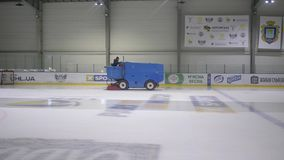 Man riding on machine cleans ice rink for entertainment and winter sports inside a hockey arena stock footage