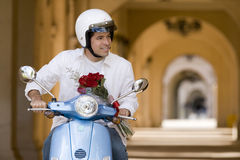 Man riding on motor scooter near colonnade, holding bouquet of red roses, smiling, front view Stock Images
