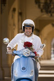 Man riding on motor scooter near colonnade, holding bouquet of red roses, smiling, front view, portrait Royalty Free Stock Image