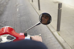 Man riding motor scooter, point of view detail of hand Stock Image