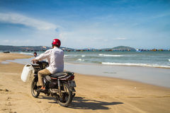 Man Riding Motorbike By The Beach. Man, wearing a red helmet, rides a motorbike on the shore of Mui Ne, Vietnam. Fishing boats are anchored in the background Stock Image