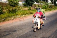 Man riding motorbike carrying heaps of fresh food. Man in colorful clothing riding motorbike carrying loads of fresh food Stock Photo