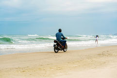 Man riding motorbike at China Beach in Danang in Vietnam. Danang, Vietnam - February 20, 2016: Man riding the motorbike at the China Beach in Danang in Vietnam Royalty Free Stock Images