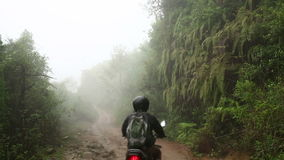 Man riding motorbike in mist, at himalayas stock video