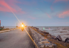 A man riding motorcycle with headlight on, at the pier Stock Photo